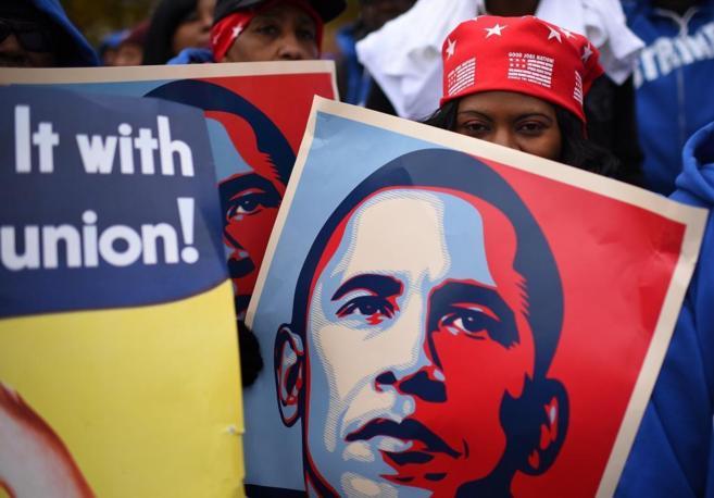 Una mujer sostiene un cartel con el rostro de Obama.