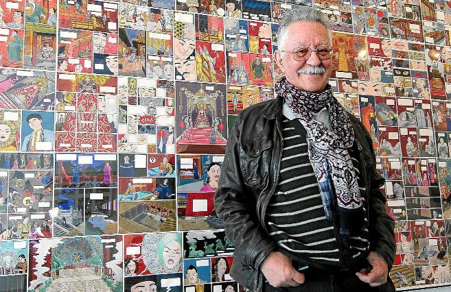 Nazario posa delante de uno de los paneles de la exposición dedicada...