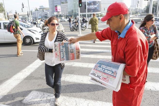 Un repartidor entrega a una ciudadana un ejemplar del 'Israel...