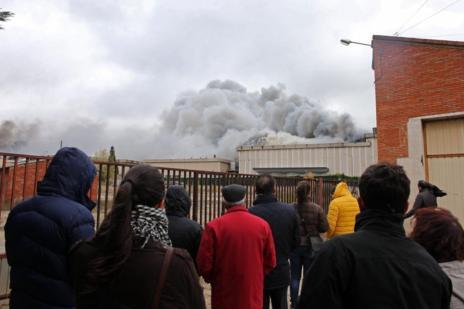 Varias personas contemplan el incendio de la fábrica de Campofrío en Burgos.