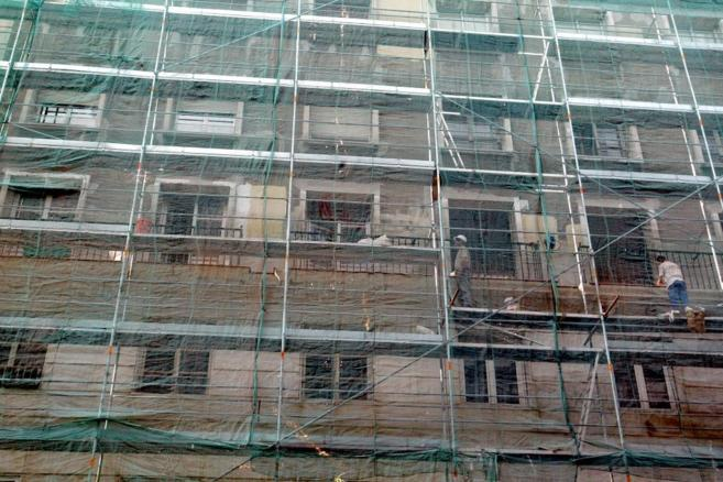 Fachada de un edificio madrileño cubierta de andamios para realizar...