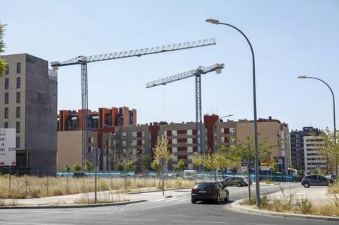 Varias grúas levantan bloques de pisos en un nuevo PAU de Madrid.