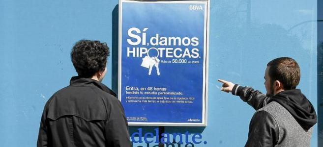 Dos jóvenes miran un cartel que publicita hipotecas en el escaparate...