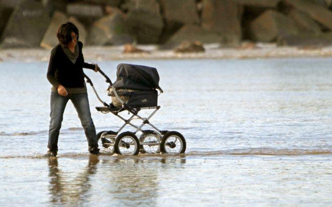 Una mujer con su bebé en la playa de la Zurriola.
