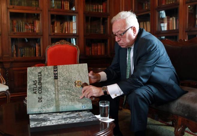 García-Margallo observa en un atlas el lugar donde fue secuestrado el...