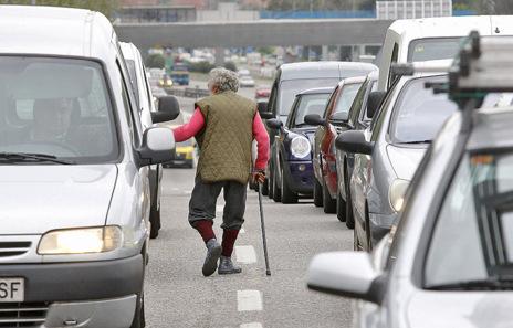 Un hombre transita entre los coches pidiendo limosna.
