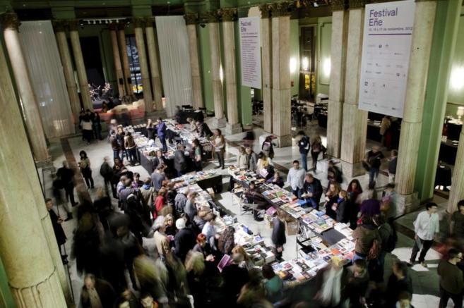 Decenas de asistentes rodean una mesa llena de libros.