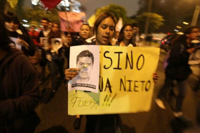 Una joven protesta por los estudiantes desaparecidos durante una...