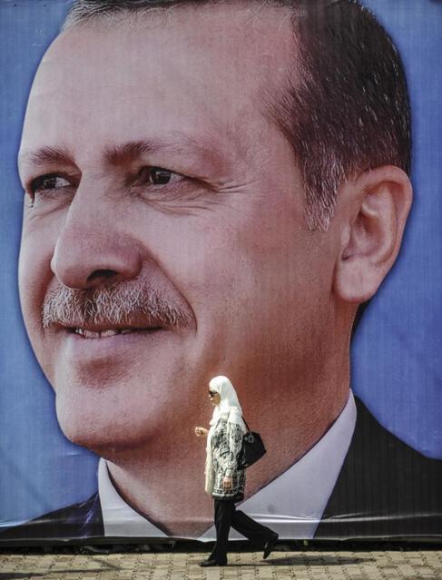 Una mujer camina frente a un póster con el rostro de Erdogan.