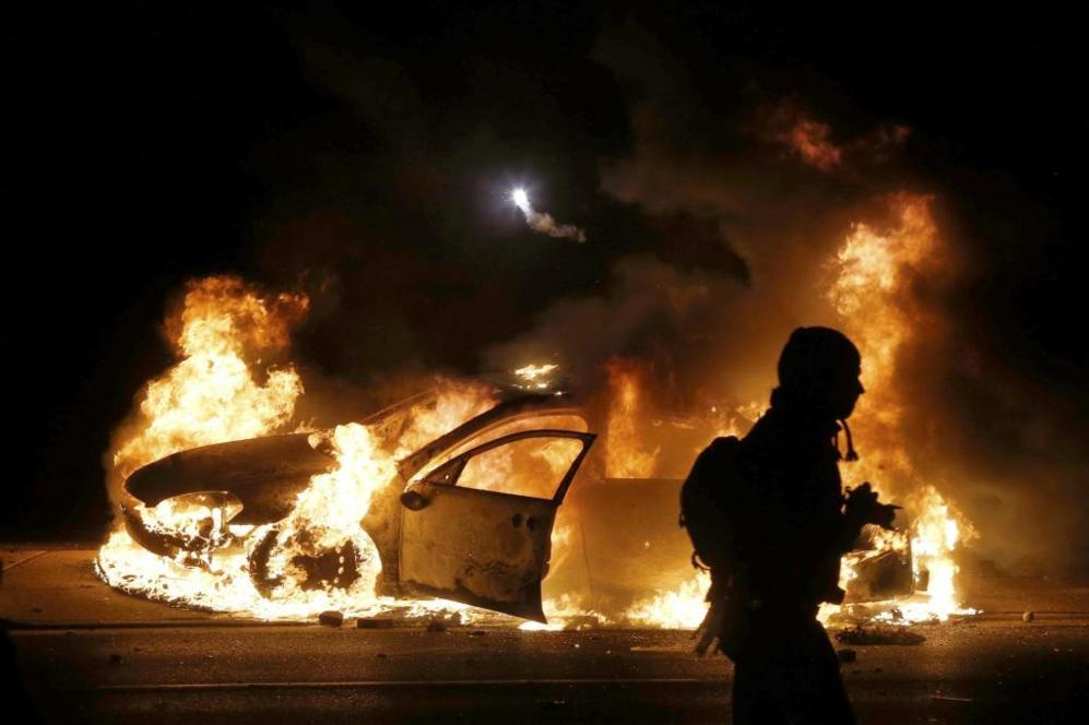 Un vehículo policial en llamas en Ferguson, Misuri.