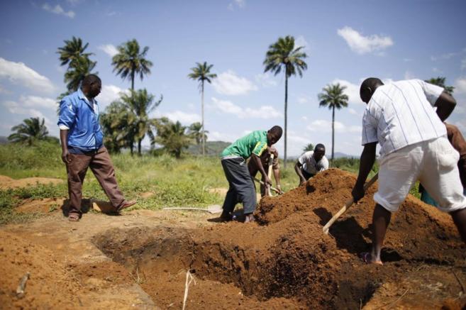 Trabajadores de Cruz Roja entierran varias víctimas del ébola en...