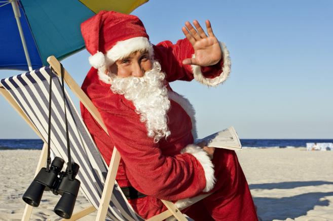 Hombre disfrazado de Papá Noel en una playa.