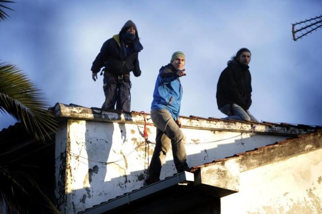 El bombero (centro) y otros dos activistas, encaramados en el tejado...