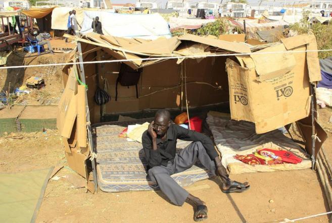 Un hombre desplazado habla por un móvil en un campamento cerca de...