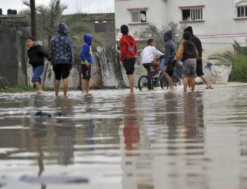 Niños palestinos juegan en una calle completamente inundada.