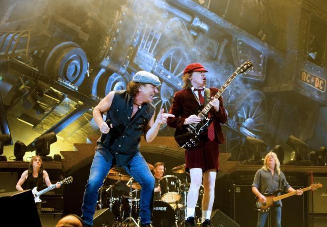 Angus (de rojo) y Brian Johnson, frente a Malcolm Young (izquierda),...