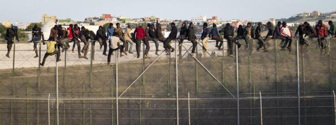 Un grupo de inmigrantes subsaharianos encaramados en la valla de...