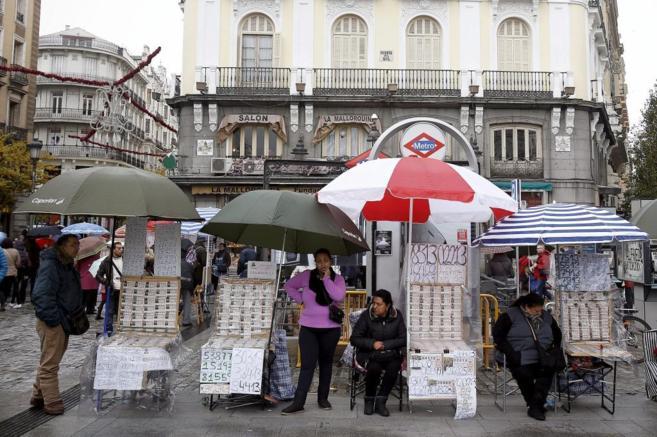 Vendedoras de lotería de Navidad junto a una boca de Metro de la...