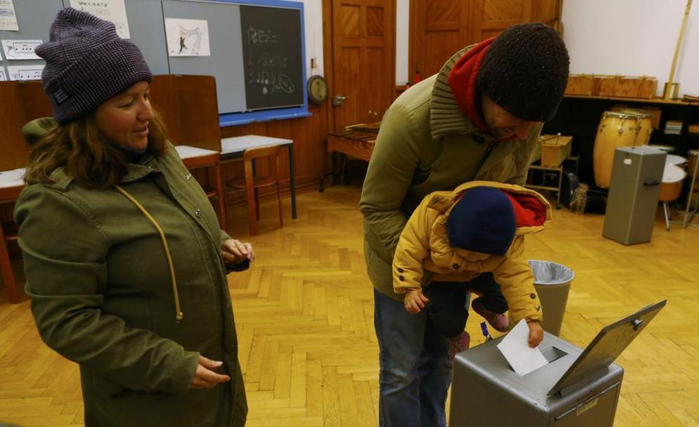 Una familia vota a primera hora en un colegio electoral de Berna.
