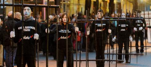 Manifetantes tras barrotes abriendo la manifestación de Bilbao