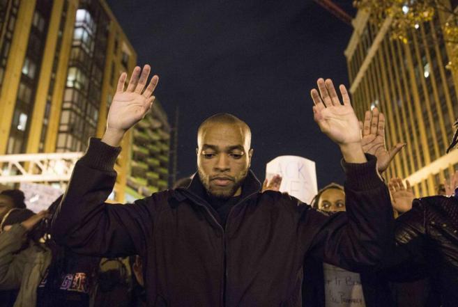 Un manifestante alza sus brazos durante una protesta por la muerte de...
