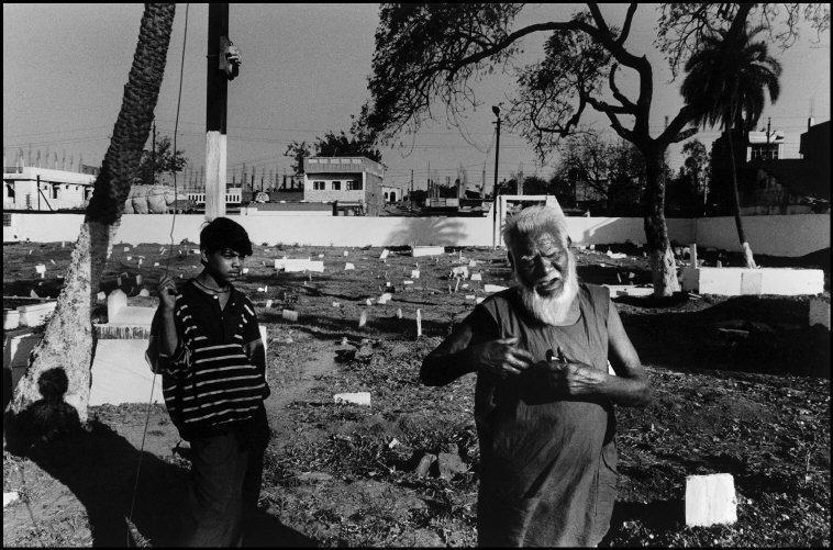 Mohammad Khan en el cementerio donde está enterrado su hijo, que...