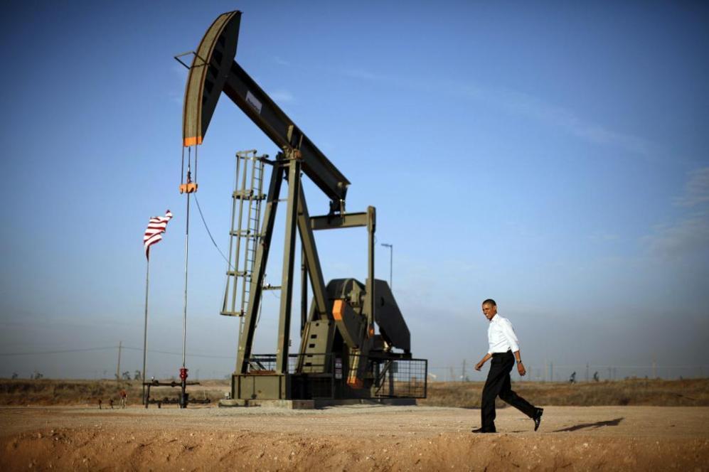 Barack Obama camina junto a una estación de bombeo de petróleo en...