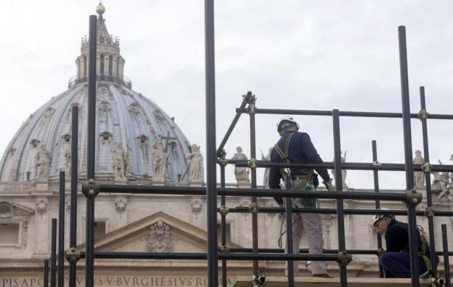 Varios operarios trabajan en la Basílica vaticana.