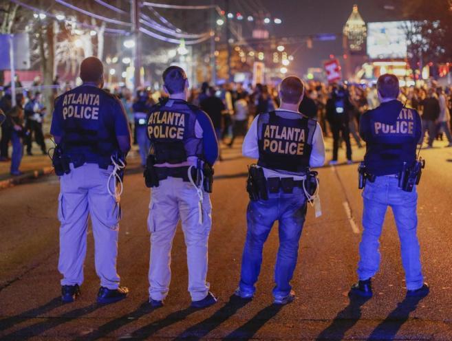 Agentes de policía frente a los manifestantes que bloquean Spring...