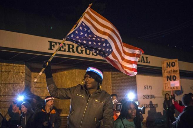 Una mujer ondea una bandera estadounidense del revés durante una...