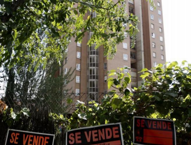 Varios carteles de 'Se vende' cuelgan en la valla de una...