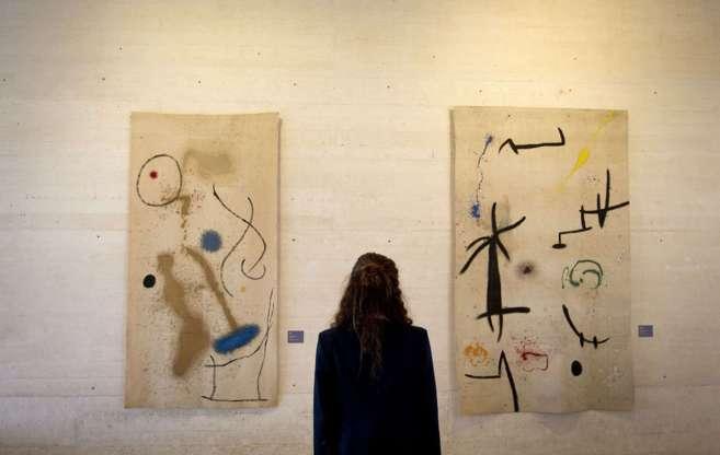 Una mujer observa dos de las obras expuestas de Joan Miró.
