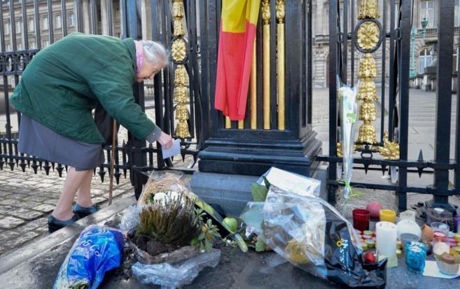 Una mujer deja una nota ante la verja del Palacio belga donde...