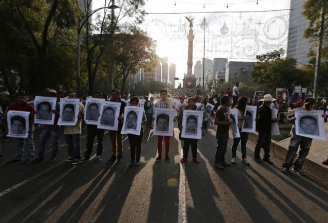 Manifestantes en México D. F. portan carteles con los rostros de los...