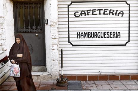 Una anciana se dispone a cruzar la calle en una zona de Ceuta habitada en su totalidad por musulmanes.