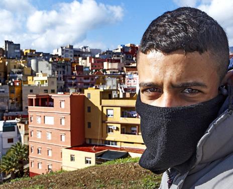 Un joven posa ante el conflictivo barrio ceutí de El Príncipe.