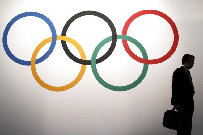 Un delegado pasa por delante de los aros olímpicos.
