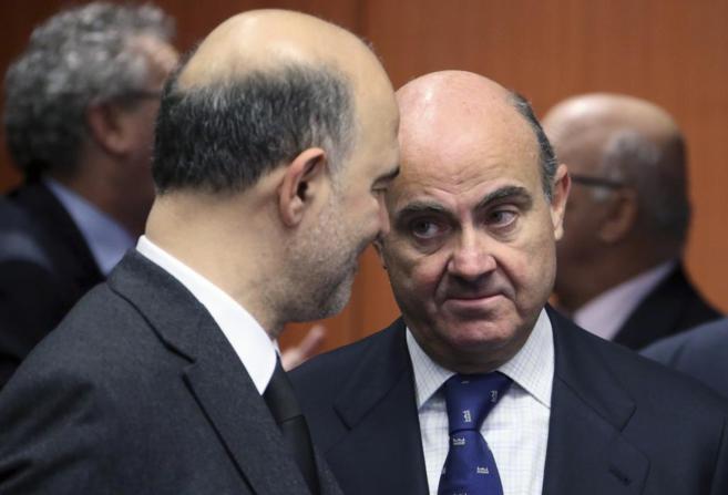 Luis de Guindos conversa con el comisario de Economía, Pierre...