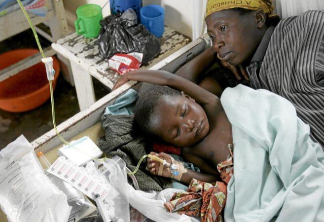 Una niña enferma de malaria duerme junto a su madre en una clínica...