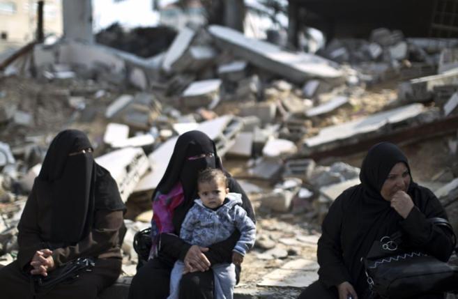 Mujeres palestina sentadas ante un edificio derruido en Gaza.