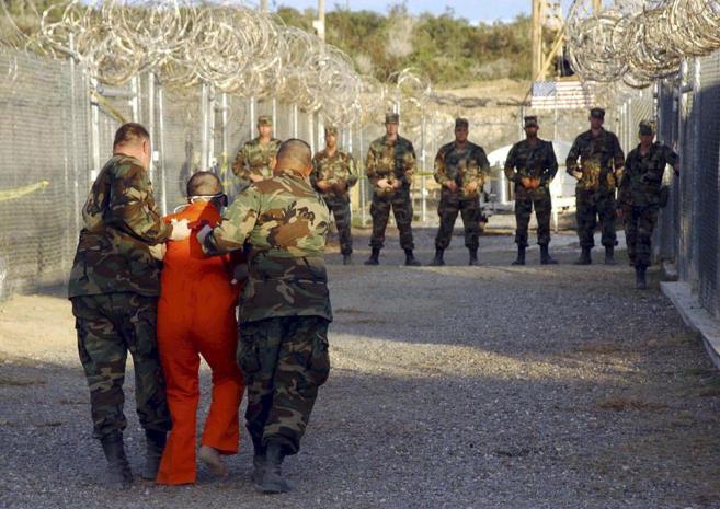 Varios soldados de EEUU trasladan a un preso de Guantánamo a su celda...
