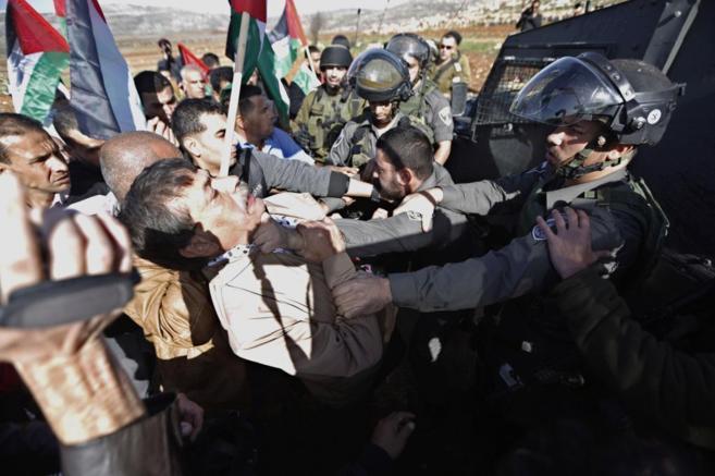 Un soldado israelí sujeta con fuerza a Ziad Abu Ein, en el choque en...