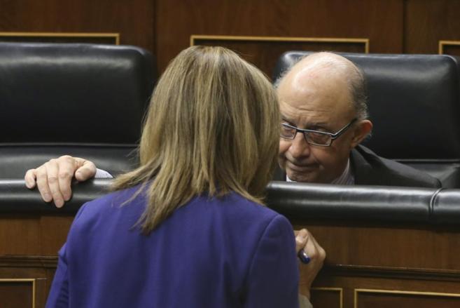 La ministra de Empleo, Fátima Báñez, de espaldas, habla con el...