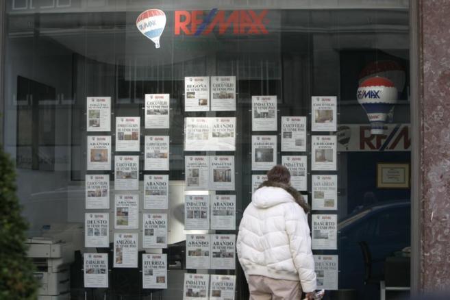 Un joven mira anuncios de pisos en el escaparate de una agencia...