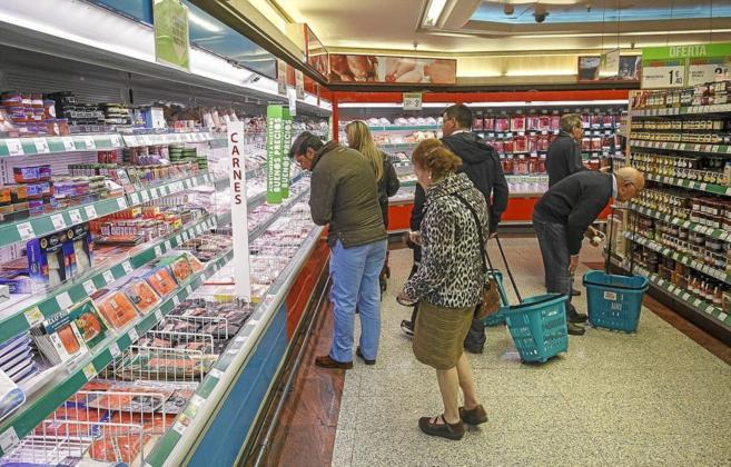 Varias personas hacen la compra en un supermercado.