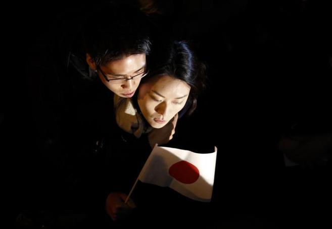 Una pareja espera la llegada del primer ministro, Shinzo Abe, a un...