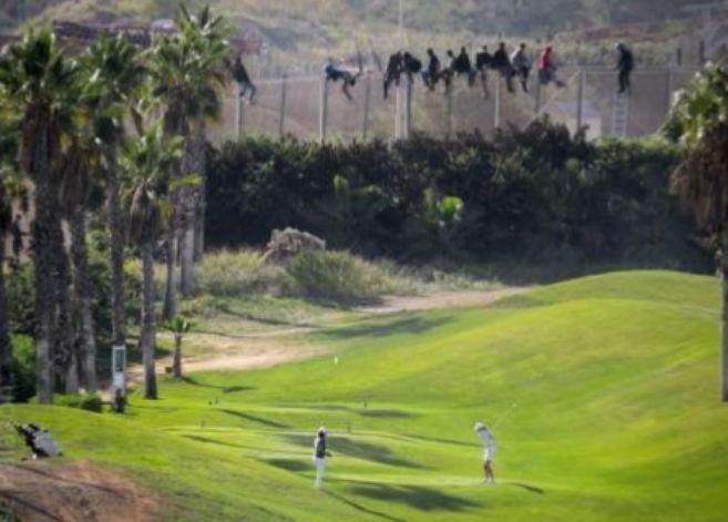 Personas jugando al golf delante de inmigrantes en la valla.