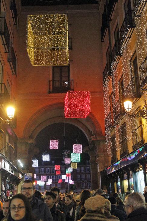 Gente camina por una calle aledaña a la Plaza Mayor, decorada con...