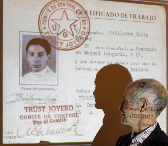 Guillermo Suils mirando la foto de su Padre en uno de los documentos...