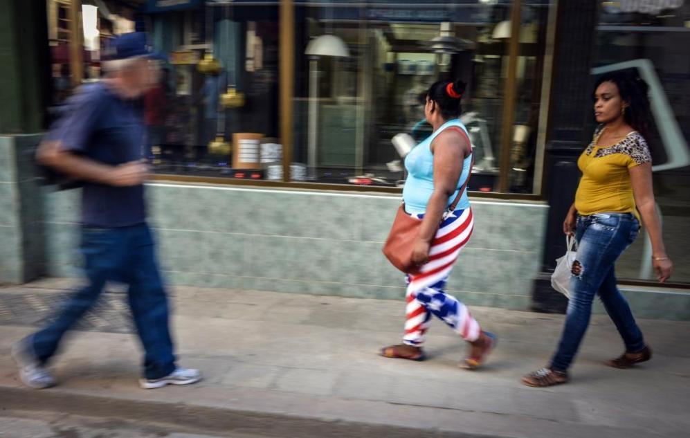 Una mujer llevando leggings con la bandera de EEUU pasea por una calle...